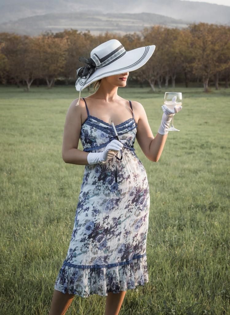 Elegantna žena u nošnji iz epohe pedesetih godina sa šeširom na glavi, čašom i cigarom u ruci