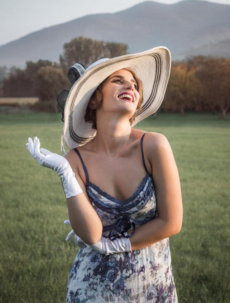 Elegantna zanosna žena u nošnji iz epohe pedesetih godina sa šeširom na glavi
