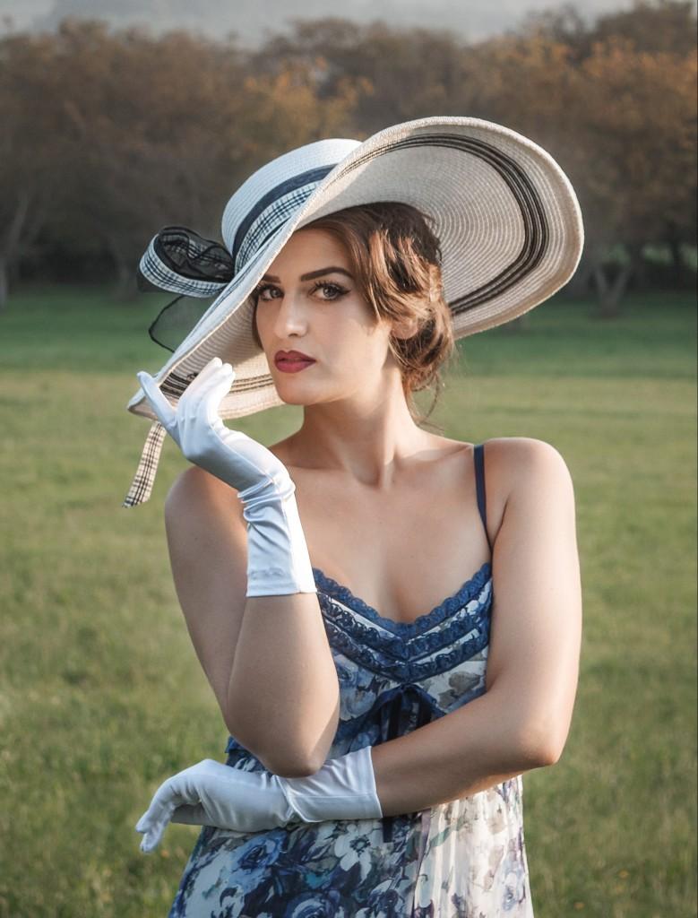 Elegantna žena u nošnji iz epohe pedesetih godina sa šeširom na glavi belim rukavicama na rukama