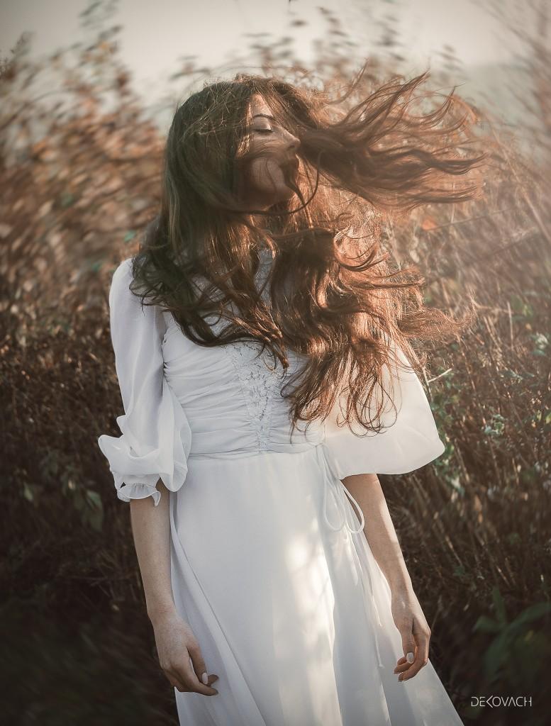 Devojka u beoj nežnoj haljini stoji u mestu dok joj vetar raspliće kosu