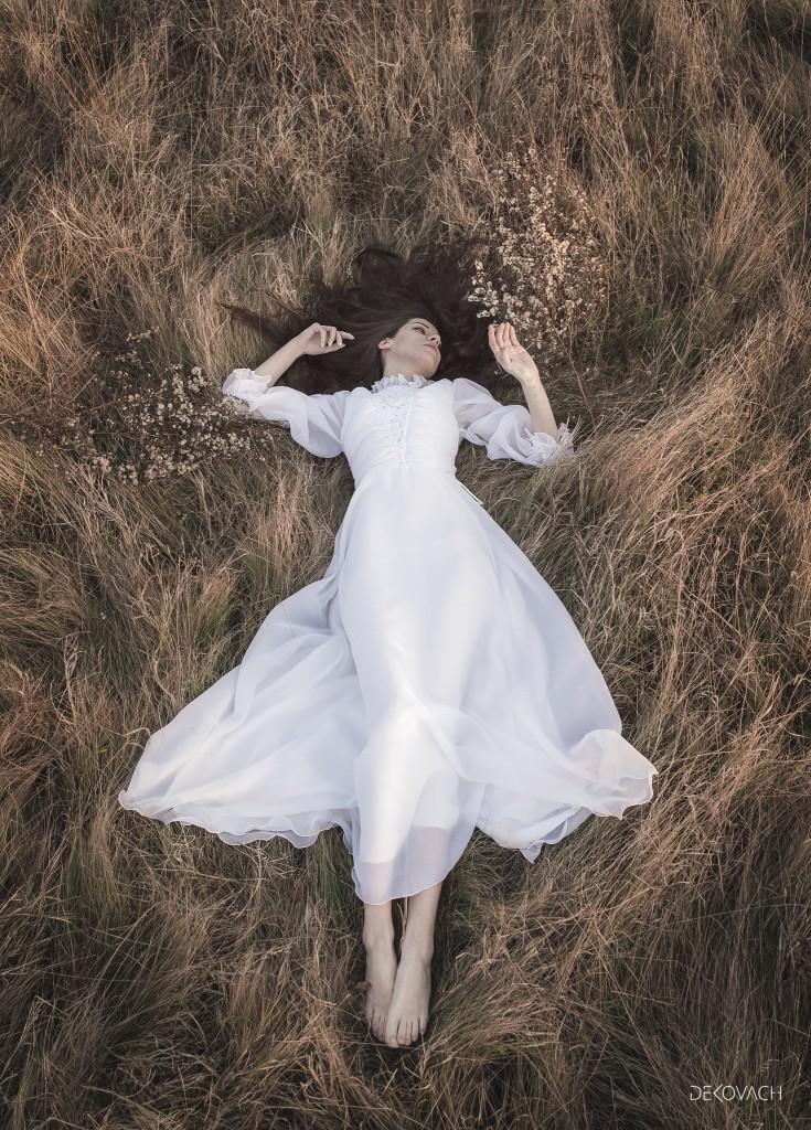 Devojka u dugoj beloj haljini leži među suvom travom i povezuje se sa prirodom oko nje
